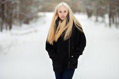 冬天画象:年轻白肤金发的妇女在摆在外面在一个多雪的公园的一件温暖的羊毛夹克穿戴了 图库摄影