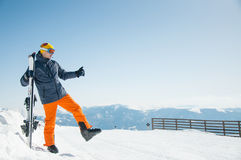 冬天滑雪胜地全景背景的愉快的滑雪者运动员 库存图片