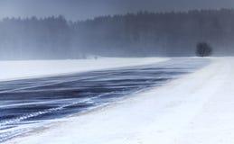 冬天 飞雪暴风雪一个多雪的风景的冬天路 在路上没有汽车 免版税库存照片