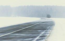 冬天 飞雪暴风雪一个多雪的风景的冬天路 在路上没有汽车 库存照片