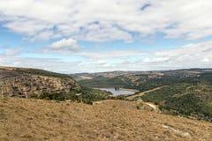 冬天VegetationHhills谷和水坝反对多云天空 库存照片