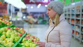 冬季衣服的妇女在超级市场摘果子 她看苹果 影视素材