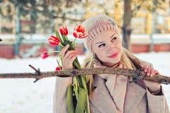 冬季衣服的美丽的白肤金发的妇女有红色郁金香的 一名愉快的妇女的纵向 库存照片