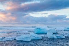 冰与黑沙子的岩石在金刚石海滩 免版税图库摄影
