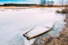 结冰入河冰,湖老木小船 被放弃的划船 免版税库存照片