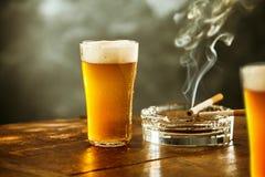 冰冷的贮藏啤酒或啤酒与一根灼烧的香烟 库存照片