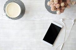 冰冻咖啡、电话和耳机在白色木桌上 免版税库存照片