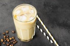 冰冻咖啡用在一块高玻璃的牛奶在黑暗的背景 复制 免版税图库摄影
