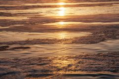 冰冻贝加尔湖的纹理在冬天在阳光下在日落 免版税图库摄影