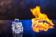 冰和火立方体在水在抽象背景浮出水面 免版税库存照片