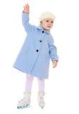 滑冰在一件蓝色外套的可爱的小女孩 免版税库存照片