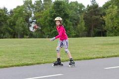 滑冰在公园的小女孩rolller 免版税库存照片