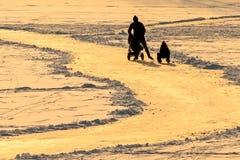滑冰在冰的家庭的剪影在日落期间在荷兰 免版税库存照片