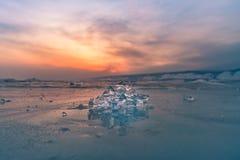 冰在冻湖有在日落天空背景以后 库存照片