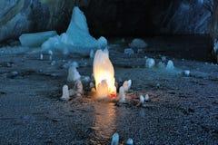 冰在大理石矿里面的蜡烛照亮的石笋 库存照片