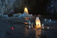 冰在大理石矿里面的蜡烛照亮的石笋 库存图片