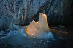 冰在大理石矿里面的蜡烛照亮的石笋 免版税库存图片