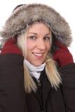 结冰在寒冷的微笑的妇女在与温暖的衣物的冬天 免版税库存照片