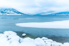 冰在有积雪的岩石海岸线和山的欧肯纳根湖 免版税图库摄影
