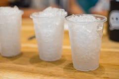 冰在木桌浅焦点的白色塑料杯子 免版税库存图片
