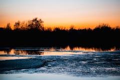 冰在河在森林里在日落 免版税库存图片