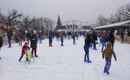 滑冰在溜冰场的孩子和成人 免版税库存图片