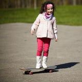 滑冰在街道上的小女孩 免版税库存图片