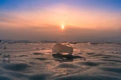 冰在贝加尔湖冬天季节的水湖有日落天空背景 免版税库存照片