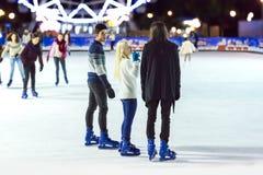 滑冰在滑冰场的少年女孩和男孩 免版税库存照片
