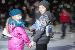 滑冰在滑冰场,冬天夜的愉快的孩子 免版税库存照片