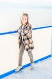 滑冰场的逗人喜爱的小女孩 免版税库存照片