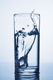 冰块滴下了入杯水 免版税库存图片