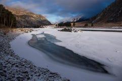 冰孔在一个五颜六色的日出和高岩石,阿尔泰山的背景的冰川覆盖的河 库存照片