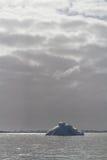 冰山在海洋,由后照在一多云天 库存图片
