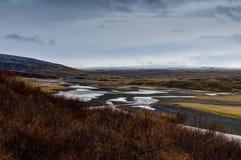 冰岛往熔岩青苔的谷视图与云彩和山 免版税图库摄影