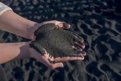 冰岛海滩黑沙子在女孩少年的手上 冰岛的大西洋海岸线 库存图片