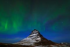 从冰岛的极光Borealis 在深蓝夜空的美好的绿色北极光与与雪, Kirkjufell,冰岛的峰顶 免版税库存照片