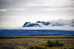 冰岛风景、绿色倾斜和山在有雾的总和 免版税库存图片