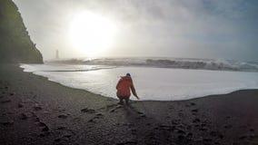 冰岛-使用与波浪的女孩在黑沙滩 库存照片