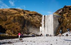 冰岛- 3月2日-旅行在假日的游人在Skogafoss瀑布,普遍的地标在冬时的冰岛201 3月02日, 库存照片