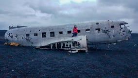 冰岛-蹲在一架被碰撞的飞机的女孩 免版税库存照片