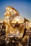 冰川和平衡的岩石与太阳星在冰岛的金刚石海滩与黑沙子 免版税图库摄影