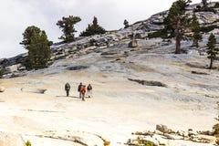 冰川圆顶岩石的四个远足者 库存照片