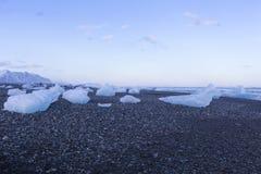 冰打破在黑沙子岩石沙子海滩自然冬天地平线背景 免版税图库摄影