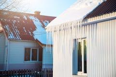 冰柱从一个房子的屋顶垂悬在乡下 免版税库存照片