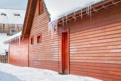 冰柱和雪在一个老木村庄 免版税库存图片