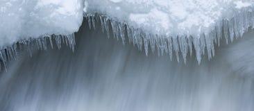 冰柱和雪近的流动的水 免版税库存照片