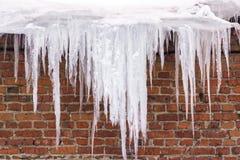 冰柱垂悬从大厦的屋顶的-对人的危险 免版税图库摄影