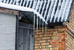 冰柱从房子的石板屋顶垂悬在雪下 图库摄影