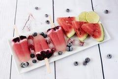 冰棍儿用西瓜、椰奶、石灰、莓和蓝莓 在一个白色长方形高原的冰棍儿,长方形冰 免版税图库摄影